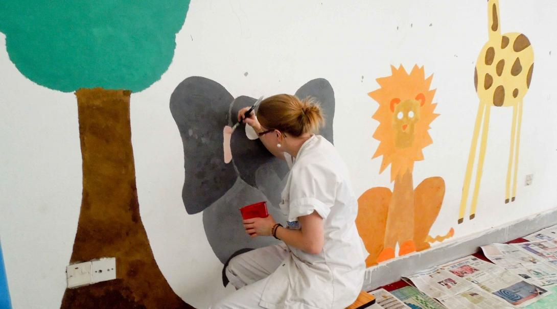 A volunteer over 50 doing childcare volunteering in Nepal, paints an educational mural on a wall.